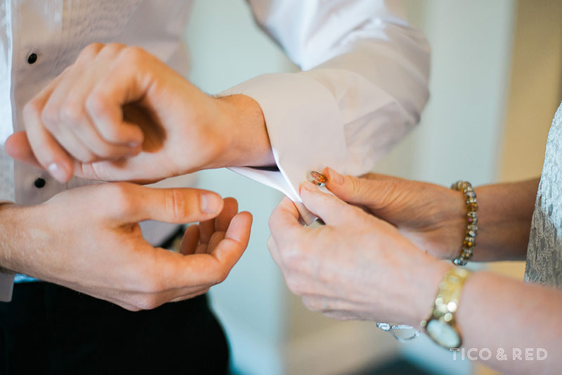 Cufflinks go on the groom before the wedding ceremony